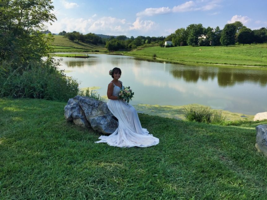 bride poses for a picture on a large stone by a lake
