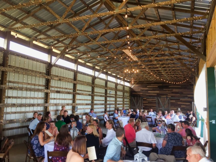 group of people at a party in a barn